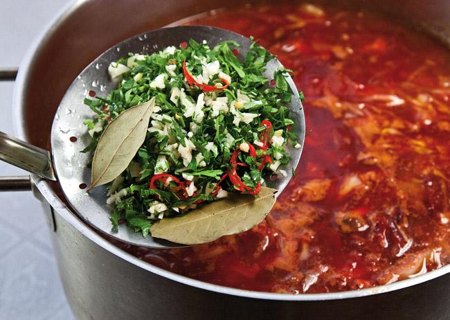 добавление зелени, чеснока и пряностей в жареный борщ