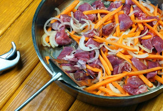 распределение мяса, моркови и лука на форме для запекания