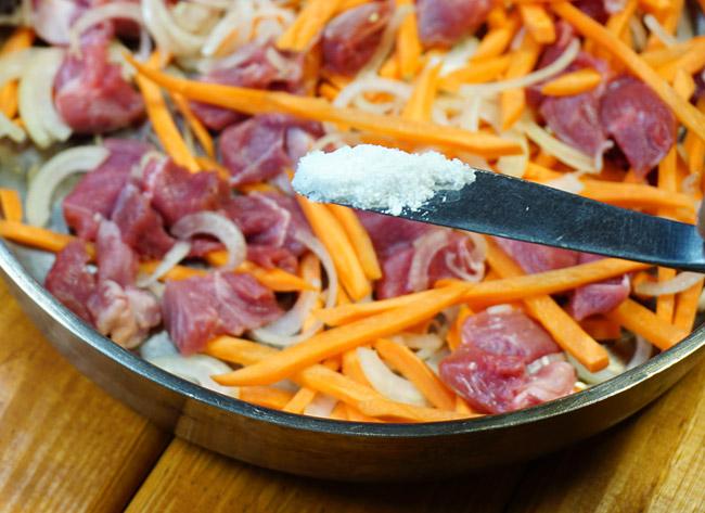 добавление соли на слой мяса, моркови и лука