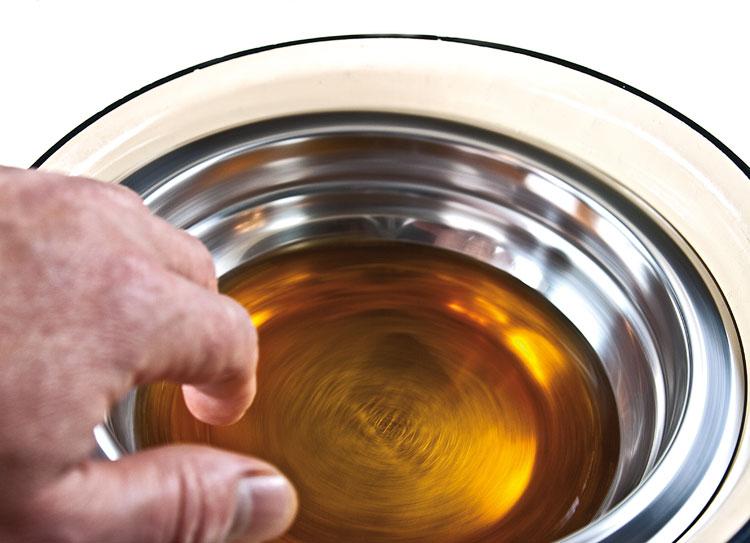 остужение сиропа в миске, погруженную в емкость с холодной водой